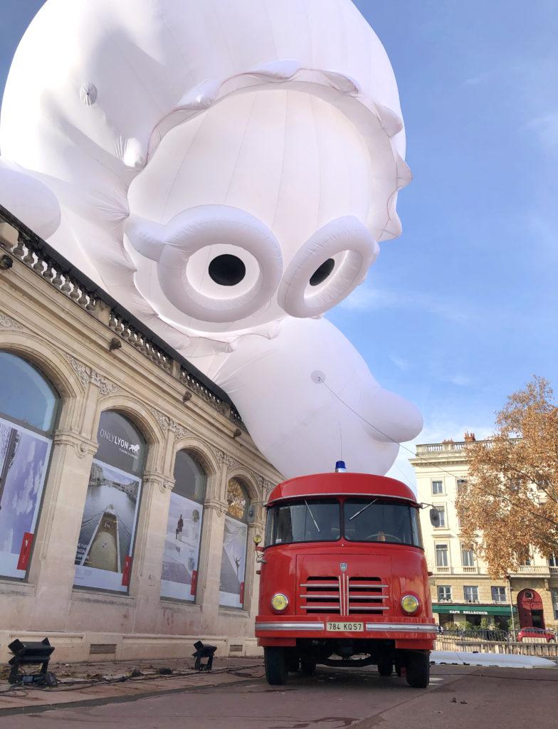 En pleine journée, un personnage gonflable joue avec un camion de pompier, place Bellecour à Lyon