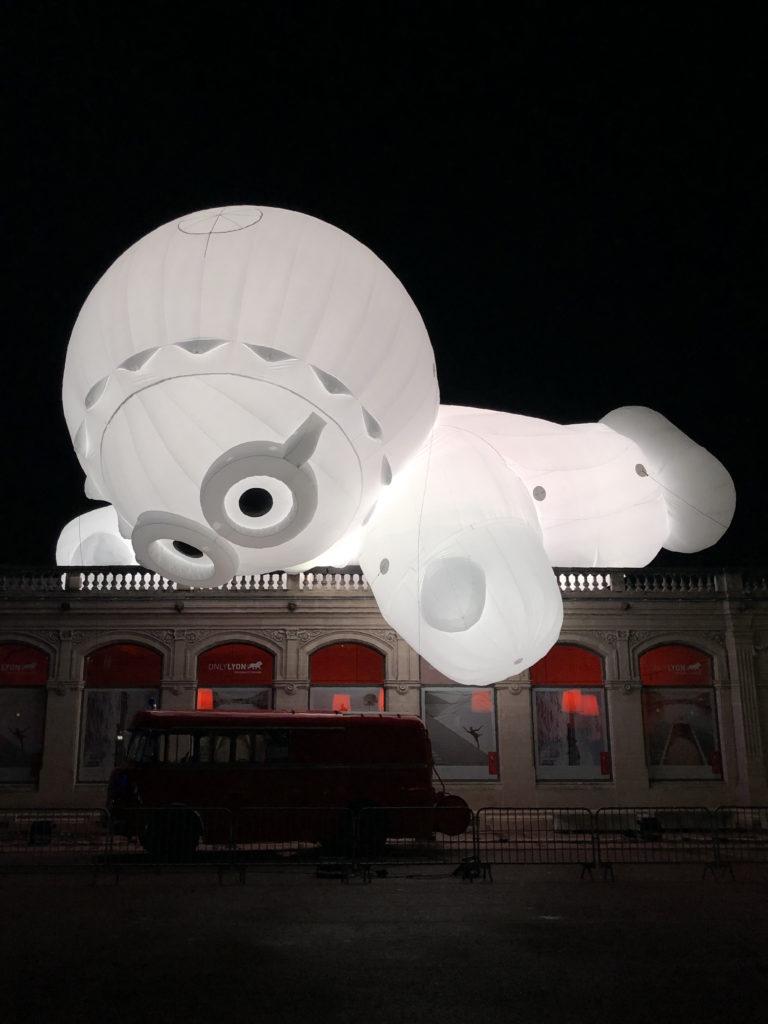 Un personnage gonflable, éclairé de l'intérieur, joue avec un camion place Bellecour, à Lyon.